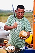 A man opening a coconut with a knife