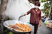 A woman frying chicken in a street in Chiang Mai, Thailand