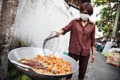 Frau frittiert Hähnchen auf der Straße in Chiang Mai, Thailand