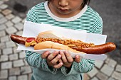 A child holding a giant sausage in a bread roll