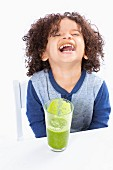 A laughing boy drinking a green smoothie