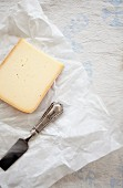 Gouda auf Pergamentpapier mit Käsespaten