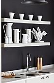 Ausschnitt einer Küchenzeile mit weisser Arbeitsplatte und eingebauter Spüle, oberhalb weiße Ablagen an schwarz getönter Wand