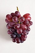 A bunch of red grapes on white surface