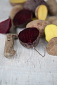 Halved beetroots and potatoes with a knife