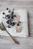Silbergabeln & Serviette dekoriert mit Schlehenzweig