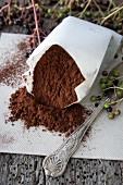 Kakaopulver in Papiertüte, daneben & im Hintergrund Holunderbeeren