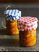 Jars of home-made chutney with checked lid covers
