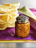 A jar of homemade chutney with a decorative metal lid