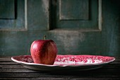 A red apple on a traditional English porcelain plate