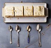 Hausgemachte Cremeschnitten mit exotischen Früchten auf Servierplatte, davor alte Teelöffel