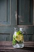 A jug of homemade lemonade with lemon and mint