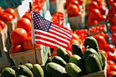 An American flag between cucumbers and tomatoes at a farmers market