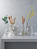 White decanters and ceramic jugs on a white table, some with flowers and some with wooden spoons