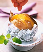A baked potato in aluminium foil being sprinkled with salt