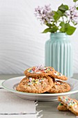 Oat biscuits with icing and sugar sprinkles with a vase of lilac flowers in the background
