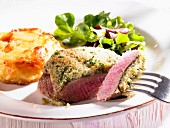 Lamb fillet with a herb crust, potato gratin and lamb's lettuce