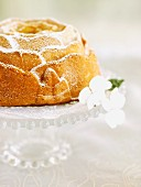 Vanilla Bundt cake with icing sugar on a glass cake stand with spring flowers