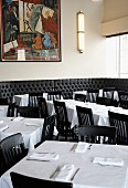 A restaurant dining room with tables laid with white tablecloths and black chairs