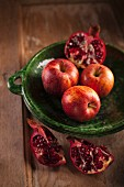 An arrangement of apples and pomegranates on a wooden table