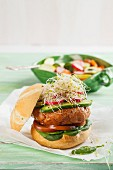 A healthy chicken burger with spinach, tomatoes, gherkins, radishes and alfalfa sprouts