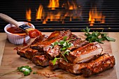 Barbecue spare ribs on a wooden board in front of a fire