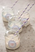 Vanilla milkshakes in jam jars decorated with stickers and striped drinking straws