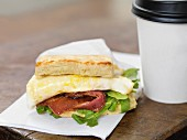 A bacon and fried egg sandwich with a coffee to go