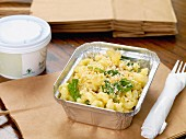 Macaroni and cheese in an aluminium container with plastic cutlery