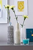 DIY-Vasen aus Flaschen mit Bindfaden umwickelt, gelbe Nelken