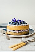 Blueberry cake with mascarpone and blueberry cream and pansies