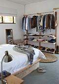 Kleiderständer mit Ablagen in schlichtem Schlafzimmer