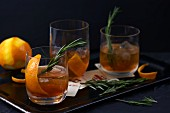 Old Fashioned cocktails with orange peel and rosemary