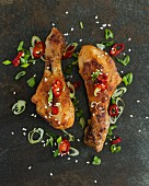 Spicy chicken drumsticks with chilli rings and spring onions