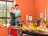 A young couple in front of a table laid with drinks and appetisers in an orange painted dining room