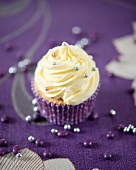 A cupcake with vanilla butter cream and silver sugar pearls