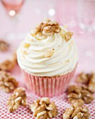 A vanilla cupcake with whipped cream and walnuts