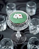 A cupcake decorated with playing cards in a glass