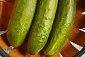 Three fresh cucumber in a wooden basket