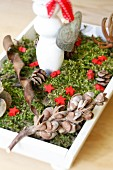 Festive table decoration in wooden dish with moss, pine cones, love-heart & stars