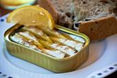 Sardinendose mit Zitronenschnitz und Brot
