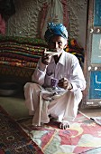 An old man wearing a turban sipping tea in front of a stack of hand made rugs, Soyla, Kachchh, Gujarat, India