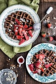 Banana and oat waffles with strawberries and maple syrup for breakfast