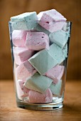 Pastel-coloured macaroons in a glass