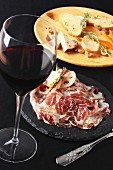 An appetiser platter with raw ham and a glass of red wine