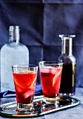 Two cocktails with hibiscus syrup, ice cubes and orange slices