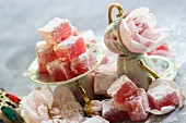 An arrangement of Turkish rose jelly with icing sugar in mocha cups and small saucers with roses in between