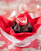 A chocolate cupcake decorated with a red fondant handbag