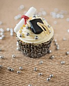 A graduation cupcake decorated with a fondant mortar board and a diploma