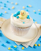 A cupcake decorated with butter cream and a fondant duckling
